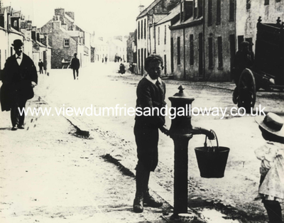 Boy filling bucket at street pump in George Street